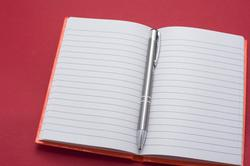 Lined blank notebook opened to the centre with a silver metallic ballpoint pen
